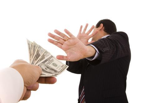 Persona de traje negro rechazando billetes